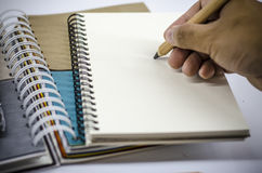 Hand which writing on blank notebook Royalty Free Stock Image
