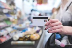 Hand with a white credit card on the background of a supermarket cash desk royalty free stock photo