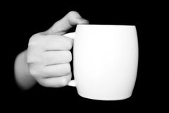 Hand with white cup isolated on black background Stock Images