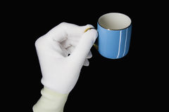 Hand in a white glove with a blue cup Stock Photography