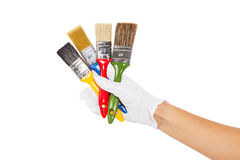The hand in white glove with colorful paintbrushes Royalty Free Stock Images