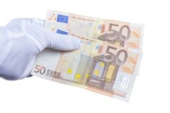 A hand with a white glove placed holds a hundred euros stock photos