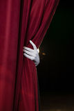 Hand in a white glove pulling curtain away Stock Image