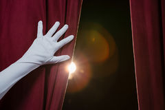 Hand in a white glove pulling curtain away Royalty Free Stock Image