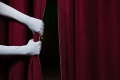 Hand in a white glove pulling curtain away Royalty Free Stock Images