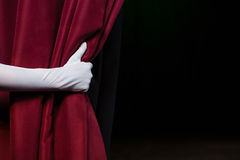 Hand in a white glove pulling curtain away Royalty Free Stock Photos