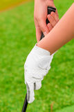 Hand with white gloves holding  a putter Royalty Free Stock Photography