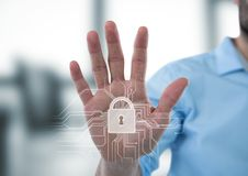 Hand with white lock graphic in blurry grey office. Digital composite of Hand with white lock graphic in blurry grey office Stock Photos