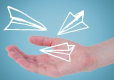 Hand with white paper airplane doodle against blue background Stock Photo