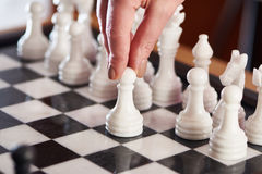 Hand with white pawn on chessboard Royalty Free Stock Photography