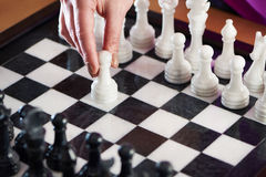 Hand with white pawn on chessboard Stock Photography