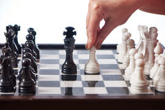 Hand with white pawn moves to black king Stock Image
