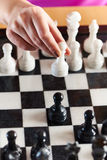 Hand with white pawn over chessboard Royalty Free Stock Photo