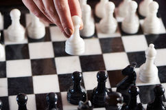 Hand with white pawn over chessboard Stock Photography