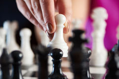 Hand with white pawn over chessboard Stock Images