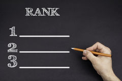 Hand with a white pencil writing: Rank blank list stock photos