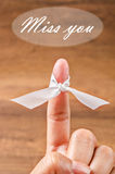 Hand with white ribbon and Miss you text. Stock Image