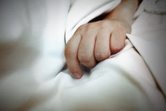 Hand on the white sheet as a concept, a metaphor of disease, ind Stock Photos