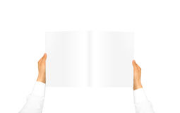 Hand in white shirt sleeve holding blank journal. In the hand. Empty magazine presentation. Pamphlet hand man. Man show pages. Sheet template. Booklet in hands Royalty Free Stock Image