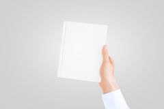 Hand in white shirt sleeve holding closed blank book. Royalty Free Stock Images
