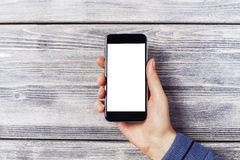 Hand with white smartphone. Blank white smartphone held by male hand on wooden background. Mock up Royalty Free Stock Photos