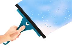 Hand with window cleaning tool. And blue sky Royalty Free Stock Image