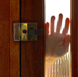 Hand on window in door Stock Images