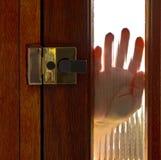 Hand on window in door. A human hand on the glass window of a hardwood door Stock Images