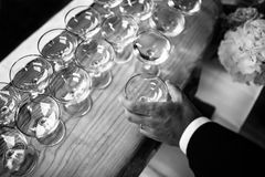 Hand with wineglass. A lot of wineglasses on a wooden table Royalty Free Stock Photography