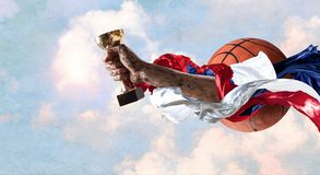 We did it. Hand of winner tighten the cup against blue sky background Stock Image