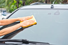 Hand wipe cleaning car glass Royalty Free Stock Photo