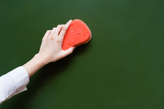Hand wipes the chalkboard, with a sponge.  royalty free stock photography