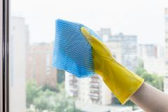 Hand wipes glass of home window by blue rag. Hand wipes glass of home window in urban apartment house by blue rag stock photography