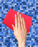 Hand wiping color tile with red rag Stock Photo