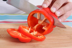 Hand With Big Knife Cutting Red Pepper Royalty Free Stock Images