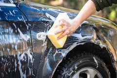 Free Hand With Yellow Sponge And Soap Are Washing The Car Stock Photo - 164435400