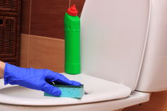 Hand of woman in blue glove cleaning toilet bowl Royalty Free Stock Photography