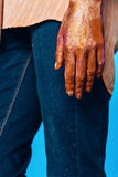Hand of woman with body art of orange glitters in denim Stock Photos