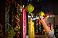 Hand of woman burning incense sticks prior to praying at temple. Joss sticks with smoke stock photography