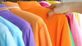 Hand of woman choosing colorful polo shirt. Close up hand of woman choosing colorful polo shirt shopping at store Royalty Free Stock Photography