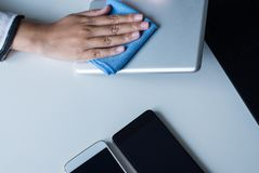 Hand woman cleaning dirty her tablet on screen with microfiber cloth. Hand female cleaning dirty her tablet on screen with microfiber cloth on table royalty free stock photos