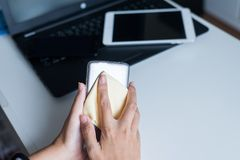 Hand woman cleaning dirty smart phone on screen with microfiber cloth. At home royalty free stock images