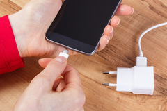 Hand of woman connects plug of charger mobile phone, smartphone charging Stock Photos