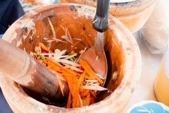 Hand of woman cooking spicy green papaya salad, carrot and herb in wooden mortar, Street food vendor make Som tam in Thailand, Tha. I papaya salad Som Tum, Thai royalty free stock photography