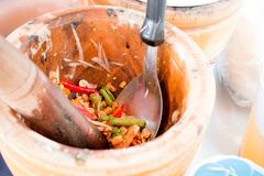 Hand of woman cooking spicy green papaya salad, carrot and herb in wooden mortar, Street food vendor make Som tam in Thailand, Tha Royalty Free Stock Photos