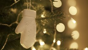 Hand woman decorating on Christmas tree with Christmas glow lights. Close-up stock footage