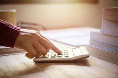 Hand woman doing finances and using calculator on table at home office. stock photos