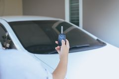 Hand woman driver holding car keys using lock door with car on background. Hand woman driver holding car keys using lock door with cars on background Royalty Free Stock Images