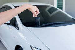 Hand woman driver holding car keys using lock door with car on background. Hand woman driver holding car keys using lock door with cars on background Royalty Free Stock Image