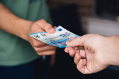 Hand of woman is giving euro money to a young man. Hand Royalty Free Stock Image